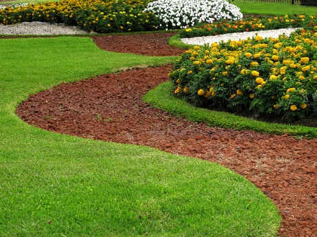 Lawn Care Carmel performing backyard landscaping services on a mulch and flower bed